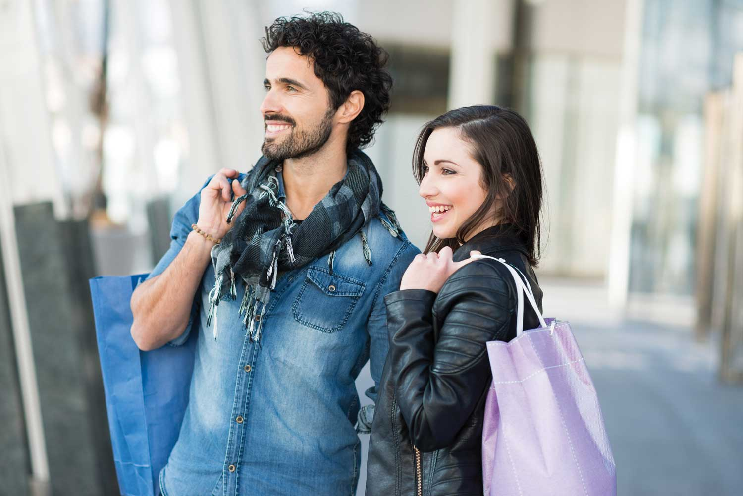 Young, hip heterosexual couple shopping outdoors, both holding shopping bags