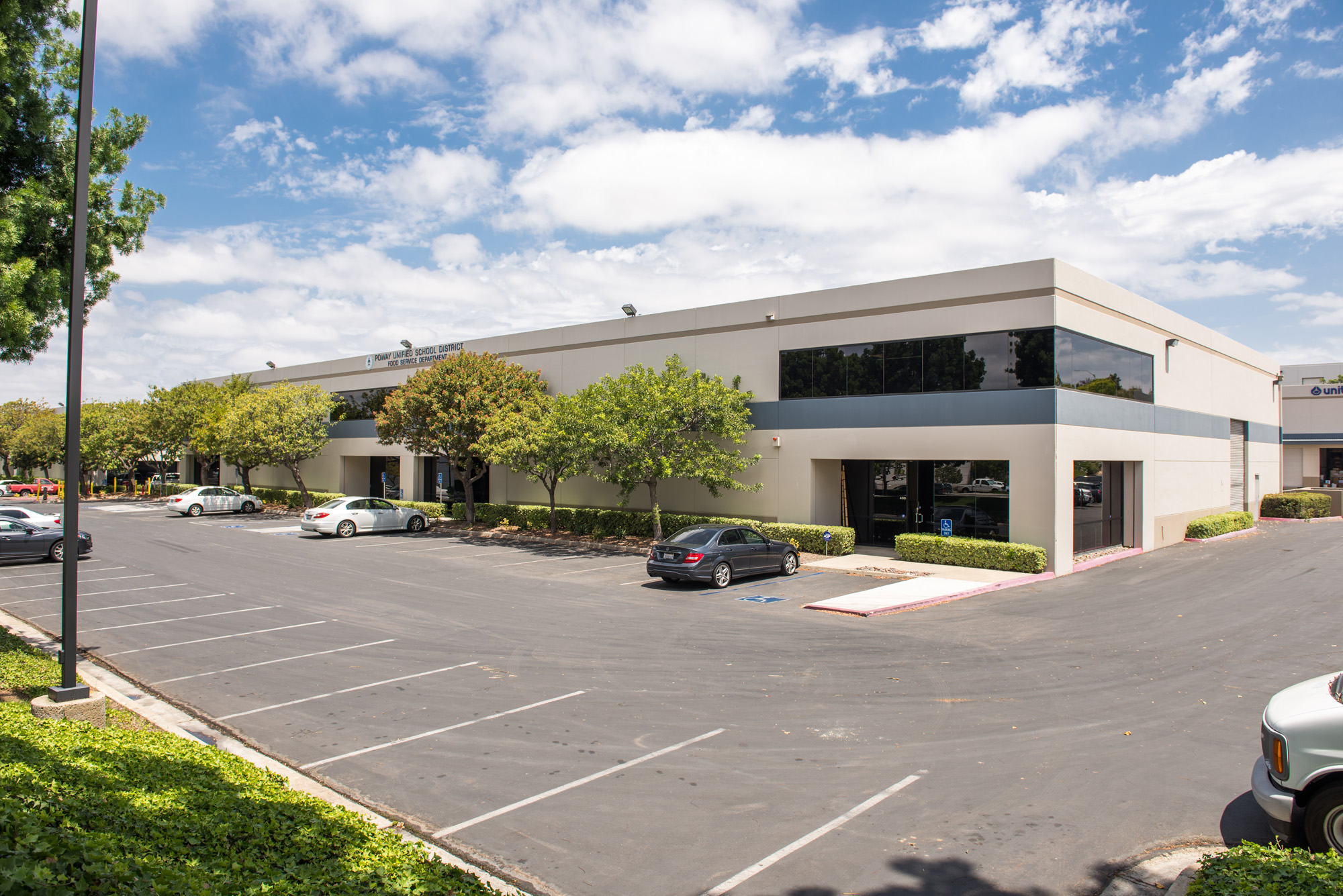 Wide-Angle Exterior photo of building entrance and roll up door at Poway Industrial Center