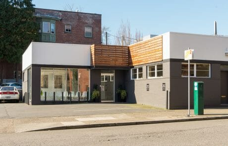 1110 SW Salmon Street is a one-story gray building with wood accents in Portland's downtown West End