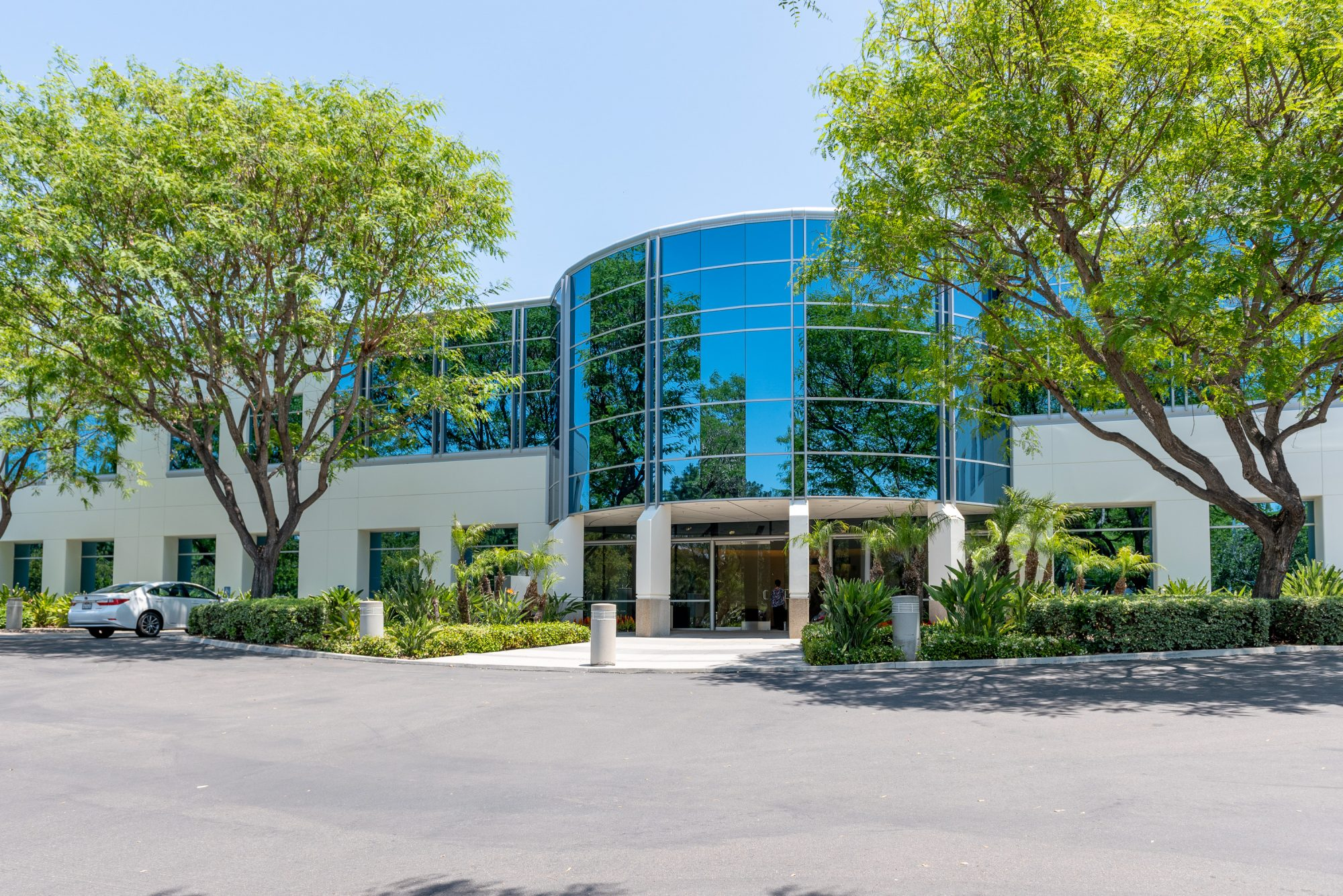 Front of carmel-corporate-plaza showing mature landscaping and glass entrance